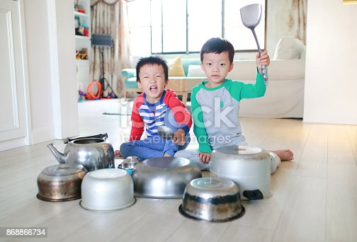 505657693 istock photo Two brother playing on floor with pots and pans 868866734