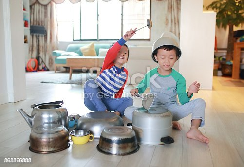 505657693 istock photo Two brother playing on floor with pots and pans 868866888