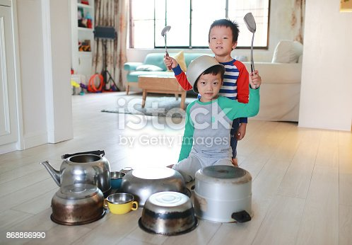 505657693 istock photo Two brother playing on floor with pots and pans 868866990