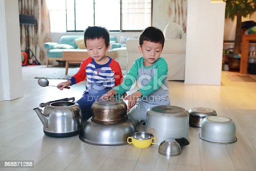 505657693 istock photo Two brother playing on floor with pots and pans 868871288