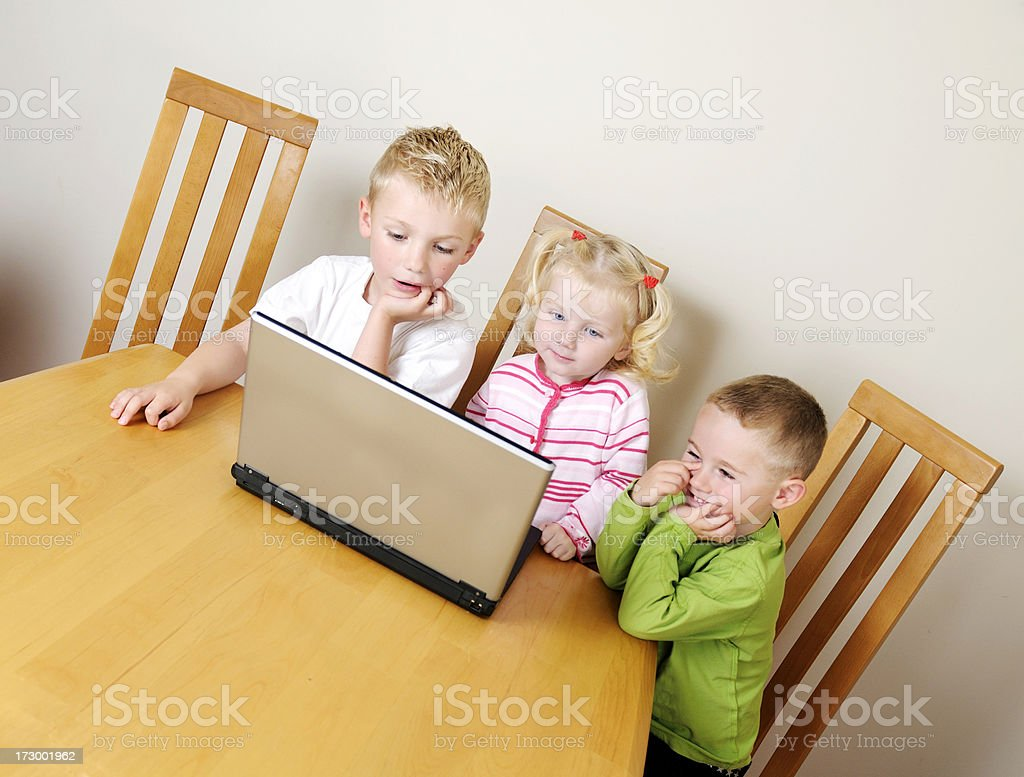 two brothers and sister using laptop royalty-free stock photo