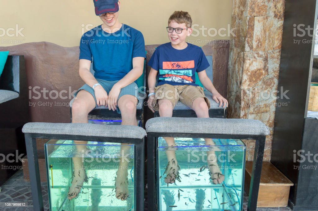 Two Brothers Enjoying Tickling Feeling of Garra Rufa Fish Therapy Pedicure on Their Feet stock photo