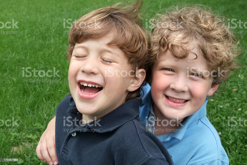 Two Brothers Hugging and Laughing Outdoors in the Summer royalty-free stock photo