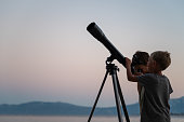 Two brothers, toddler boys, looking at the stars using a telescope by the sea on a beautiful summer night.