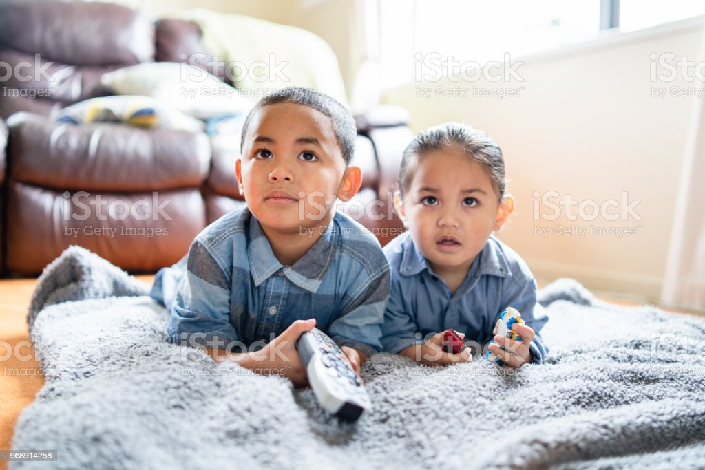 Two brothers lying down and watching TV. stock photo