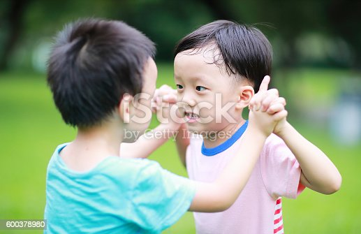 istock Two brothers play in the park 600378980