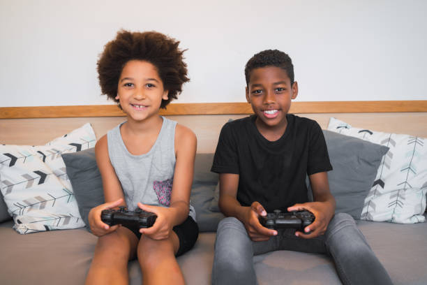 Two brothers playing video games at home. stock photo