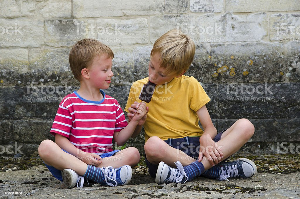 Two brothers sharing a lollipop stock photo