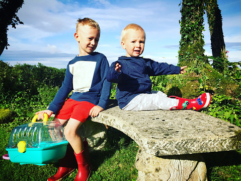 Two brothers sit on a stone seat in the garden