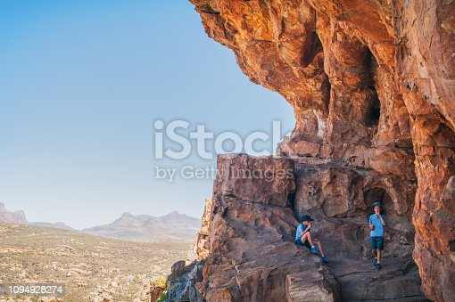 Two Young Adventurous Caucasian Boys in a Sandstone cave at Truitjieskraal in the Cederberg Wilderness Area with Sneeuberg landscape in the background South Africa