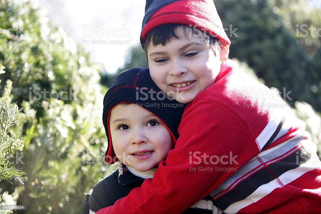 Two brothers with autism show affection outdoors during Christmas. stock photo