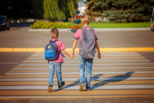 Two brothers  with backpack walking, holding on warm day  on the stock photo