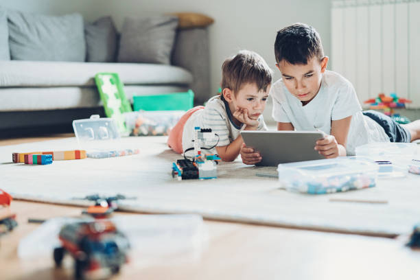 Two brothers with digital tablet and plastic blocks lying on the floor stock photo