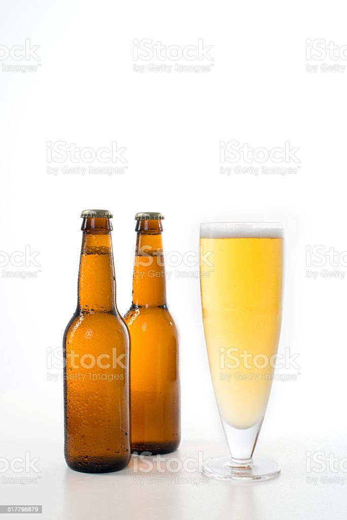 Two brown beer bottles and a glass of beer. stock photo