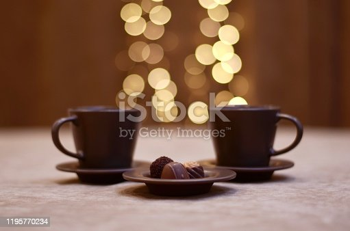 Two coffee cups of dark brown color with saucers and a plate with three candy pyramids in the shape of a chocolate cone, soaring from above with bright lights, bokeh, on a velvet background.