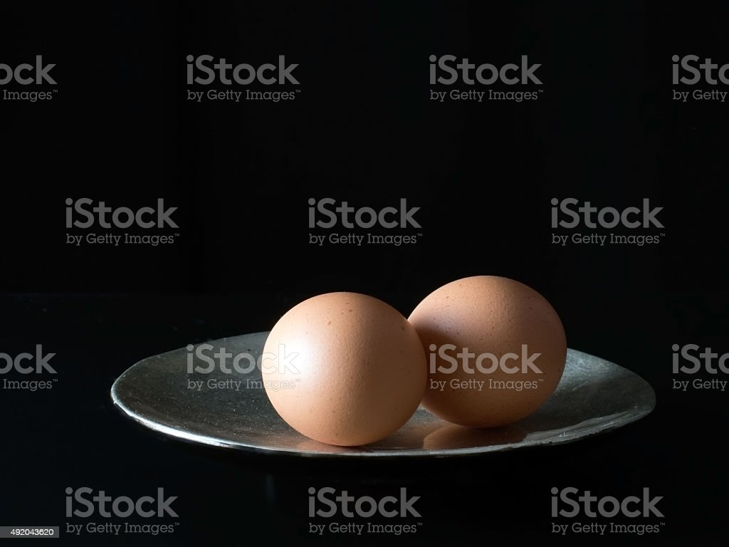 Two brown eggs on a plate, sidelit. Dark background. stock photo
