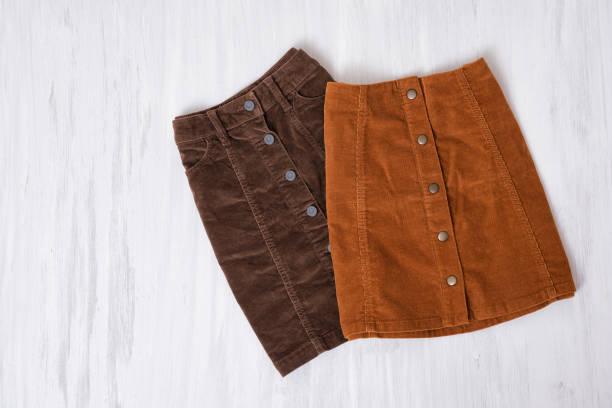 two  brown skirts on a wooden background. fashion concept - spódnica zdjęcia i obrazy z banku zdjęć