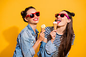istock Two brunette hair lady isolated on yellow vivid background in glasses spectacles make beaming white toothy smile eating sugar tasty appetiser snack 1092712436