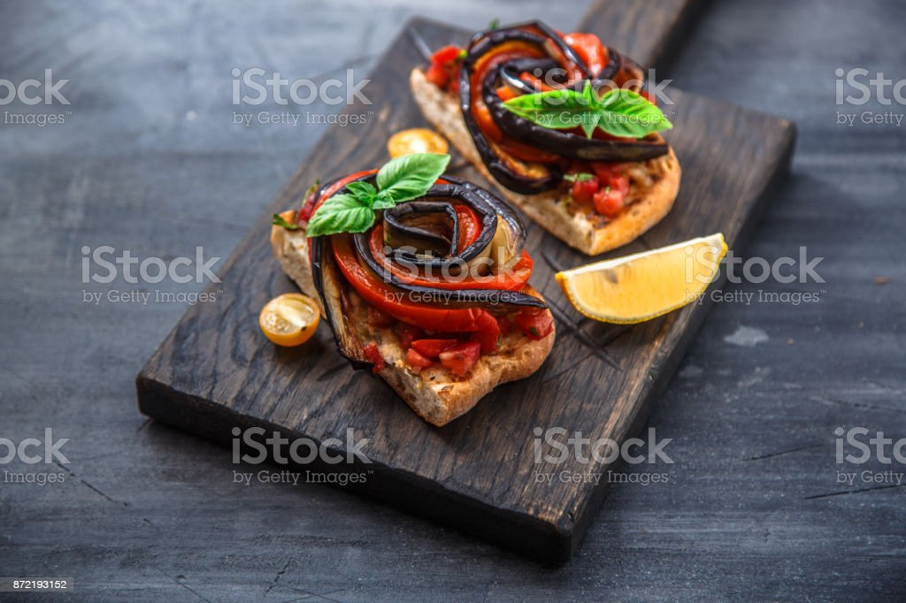 Two bruschettas with baked aubergines and peppers on black background stock photo
