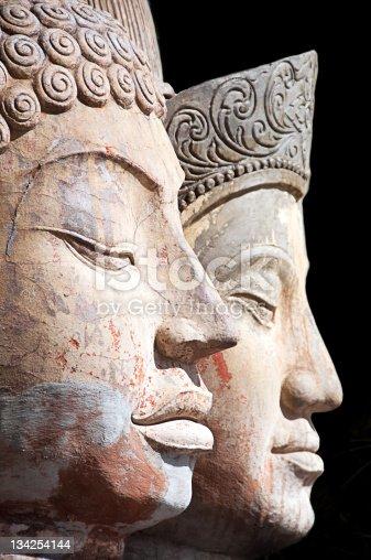 Two Stone Buddha heads on black