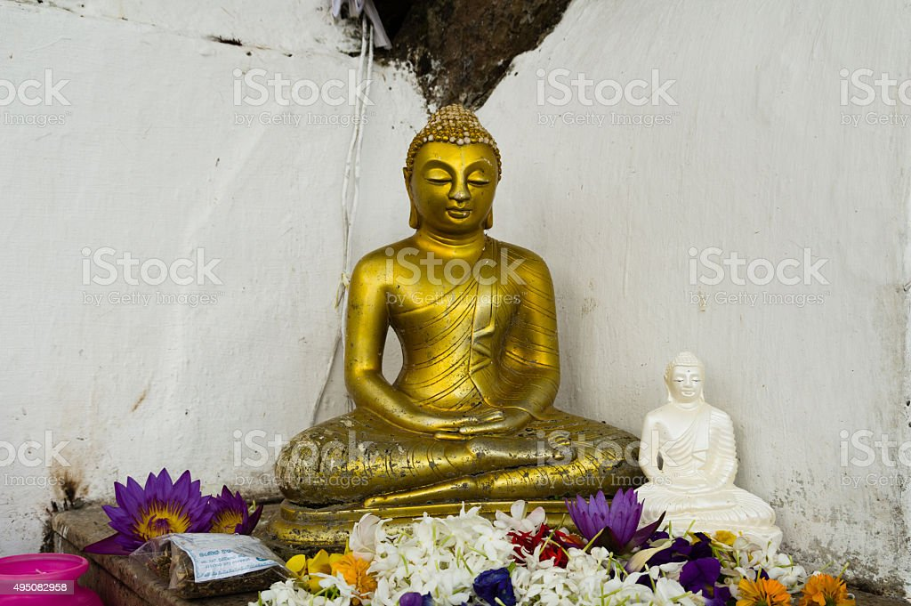 Two Buddha Statues with Flowers stock photo