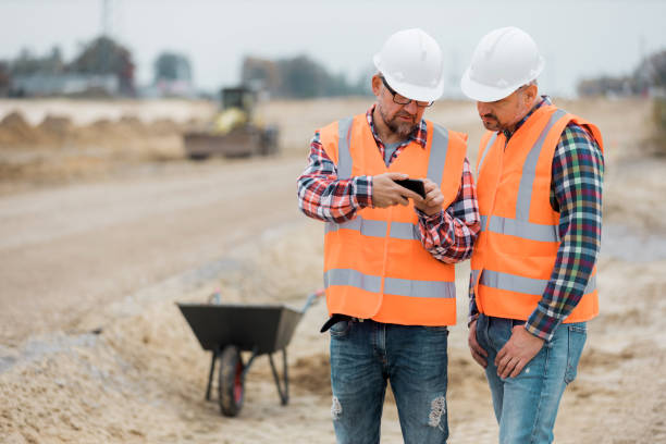 Two builders checking road construction plan on the phone