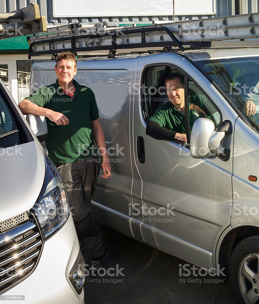 Two builders ready for work with their vans at a site stock photo