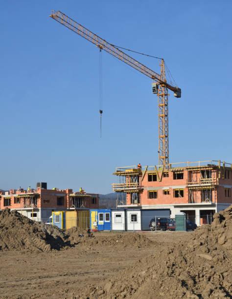 Dos edificios en proceso de construcción con grúa torre detrás de ellos - foto de stock