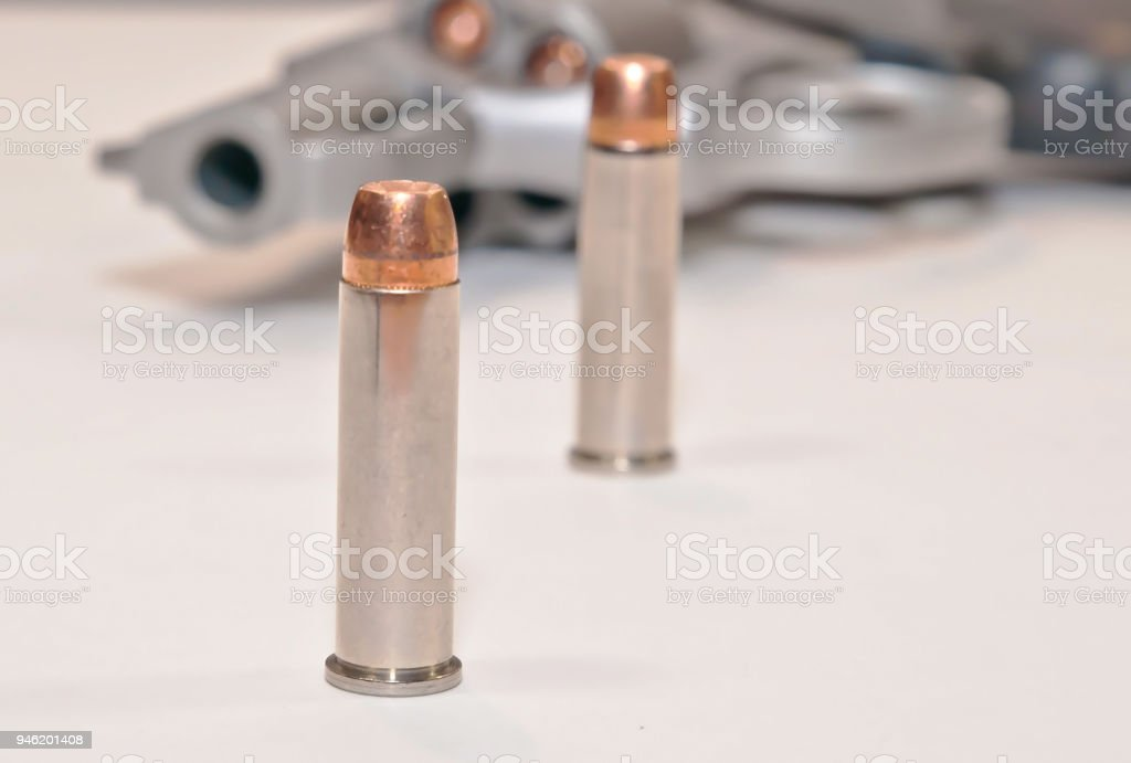 Two bullets in front of a loaded revolver stock photo