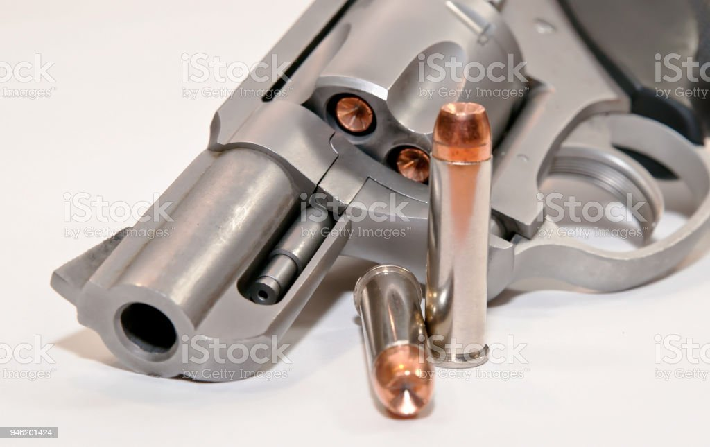 Two bullets in front of a revolver stock photo