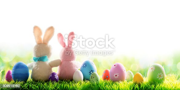 istock Two Bunnies With Easter Eggs Isolated On Sunny Meadow 509919160