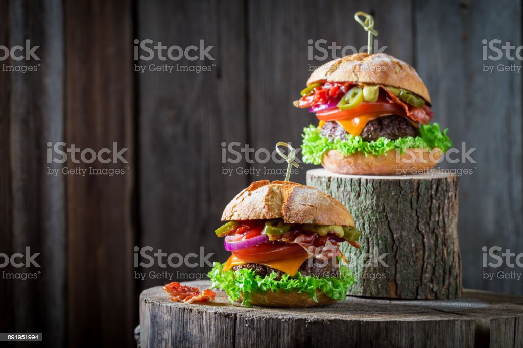 Two burger with onion, tomato and lettuce and bacon stock photo
