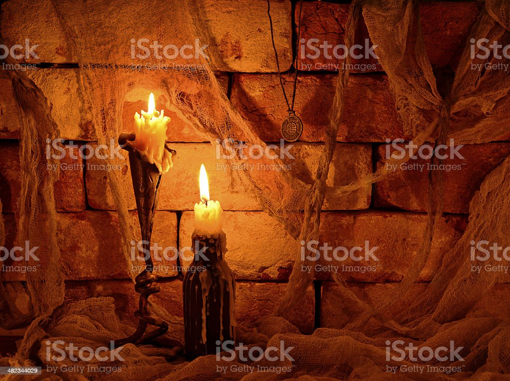 Two burning candles on brickwall stock photo
