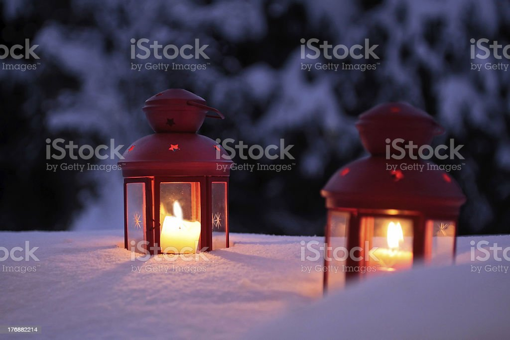 Two burning lanterns in the snow royalty-free stock photo