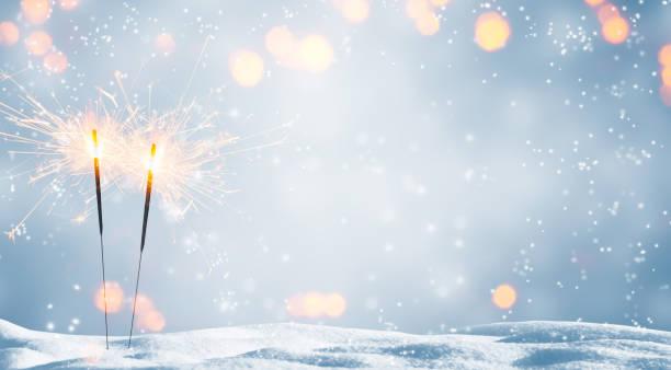 dos bengalas ardiendo en la nieve - año nuevo fotografías e imágenes de stock