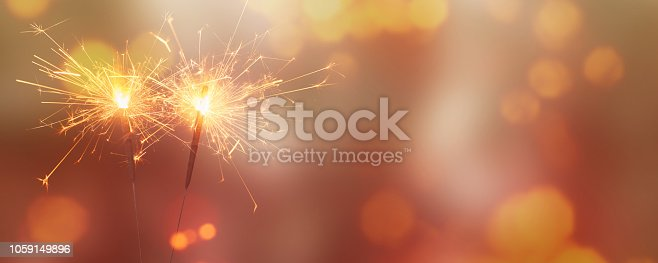 istock two burning sparklers on abstract background 1059149896