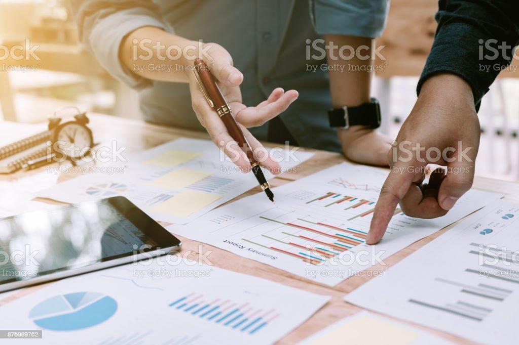 Discussão de negócios dois povos asiáticos e apontando no gráfico do relatório resumido e falando sobre resultado anual. - foto de acervo