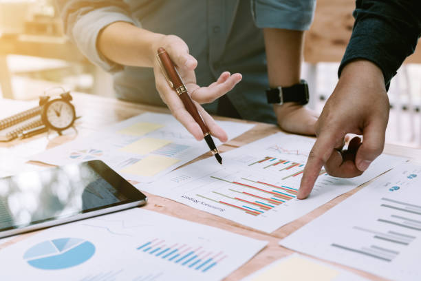 Two business asian people discussion and pointing on summary report chart and talking about annual result. stock photo