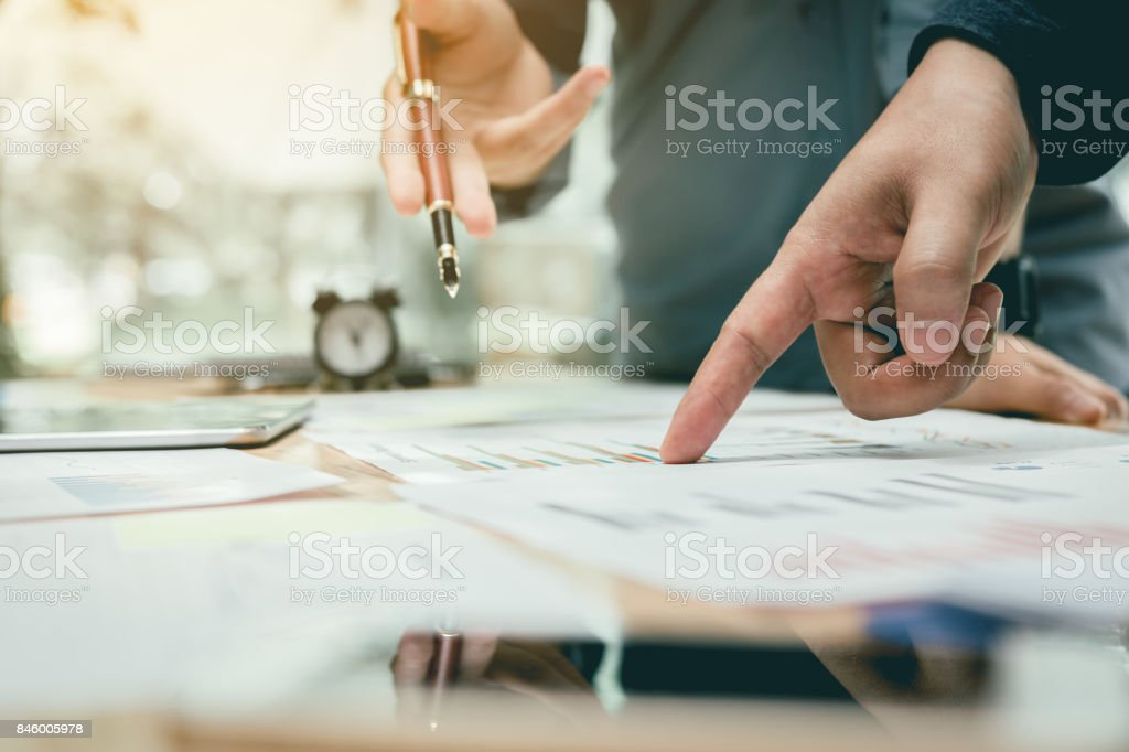 Two business asian people pointing on summary report graph and talking about annual result. stock photo