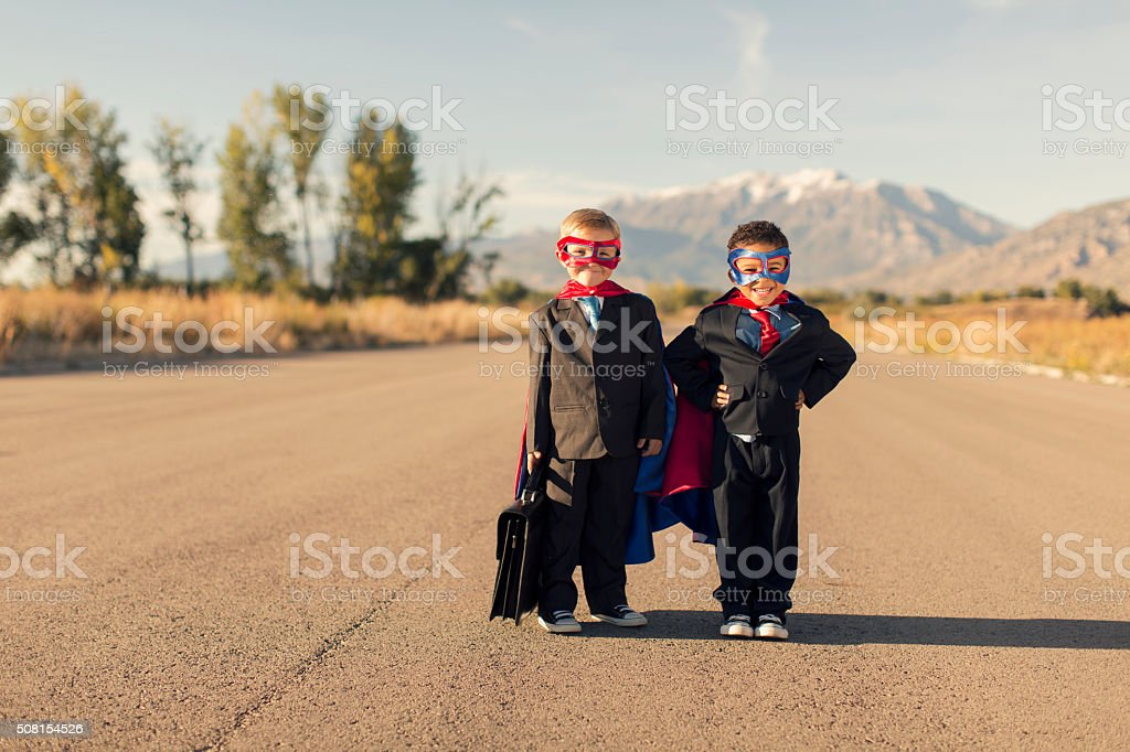 Two Business Boys Dressed in Superhero Costumes stock photo