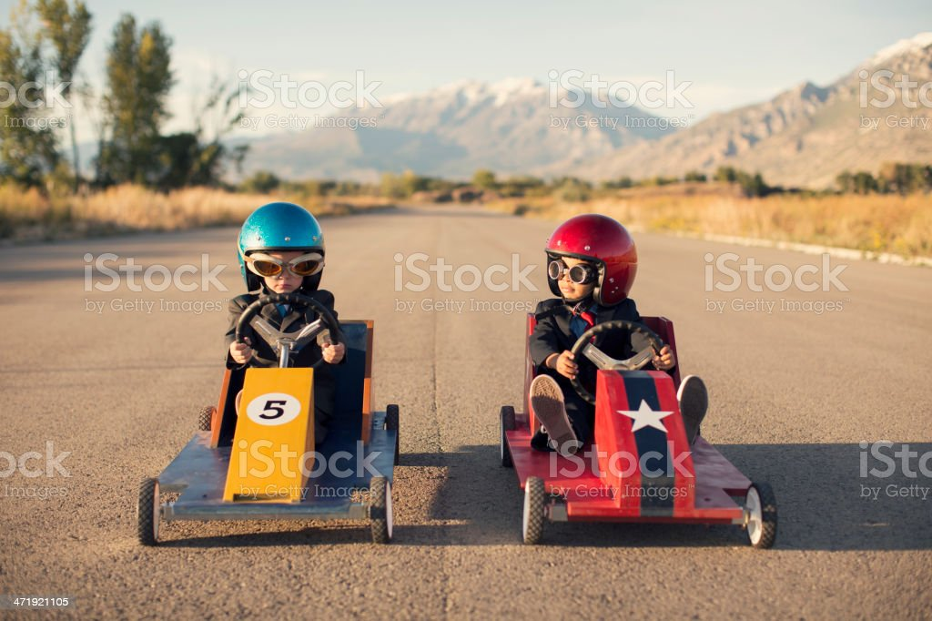 Two Business Boys Sit in Toy Cars on Street stock photo