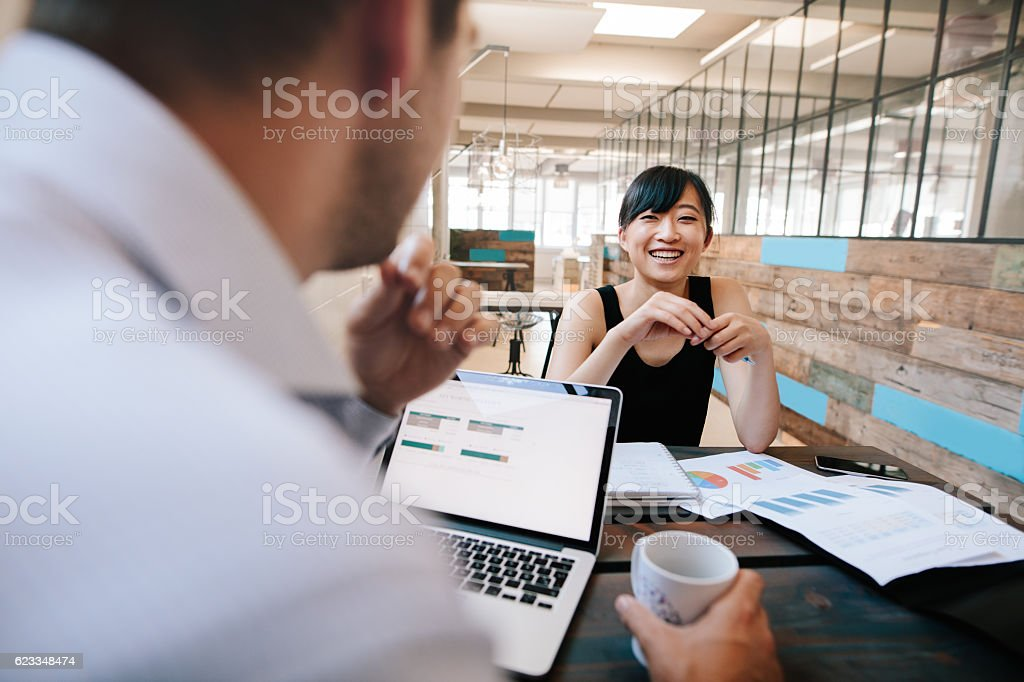 Two business colleagues discussing work in office stock photo