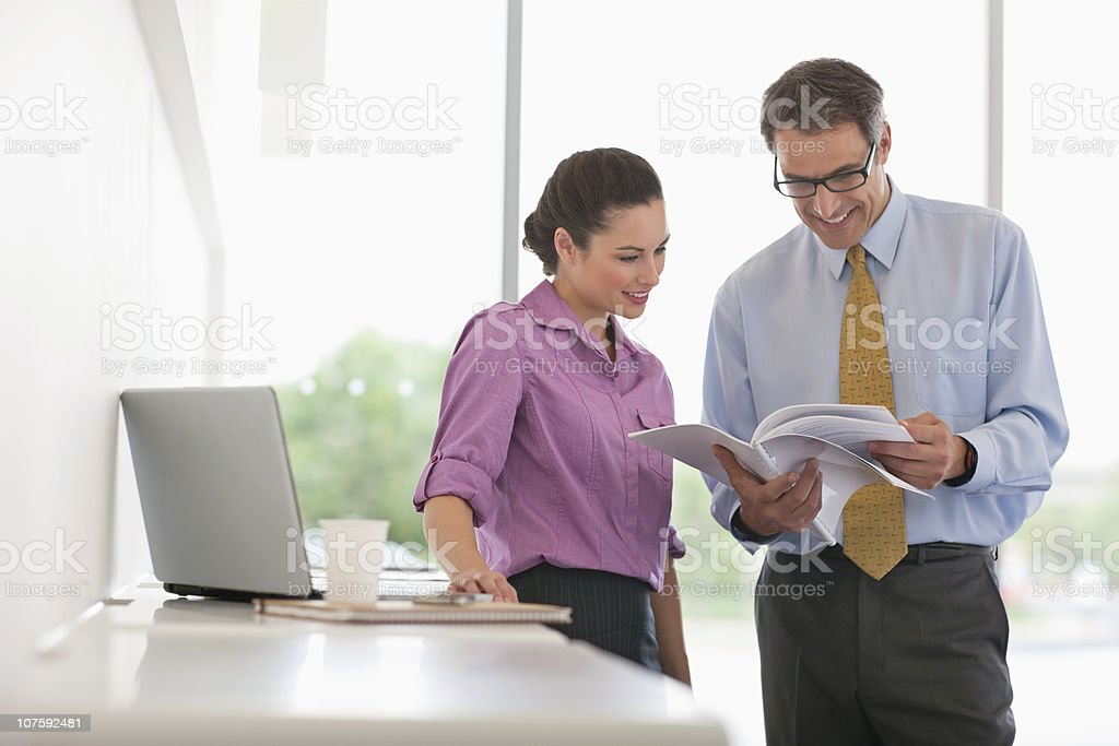 Two business colleagues looking at document with laptop in office cafeteria royalty-free stock photo