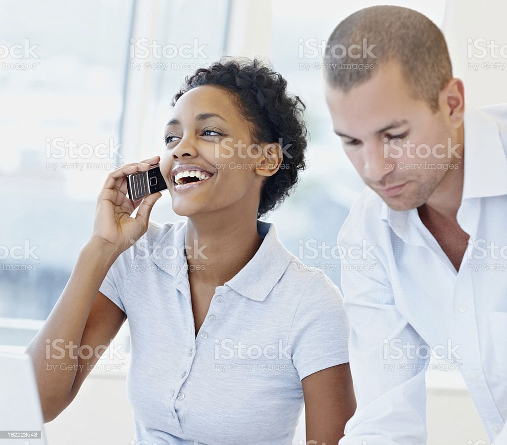 Two business colleagues while woman talking on cellphone royalty-free stock photo