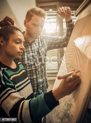 497812268 istock photo Two business colleagues writing a business plan on a whiteboard. 672801952