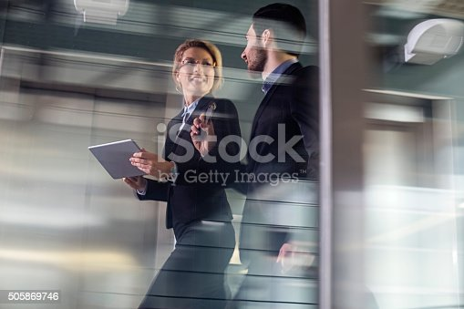 istock Two Business coworkers walking along elevated walkway 505869746