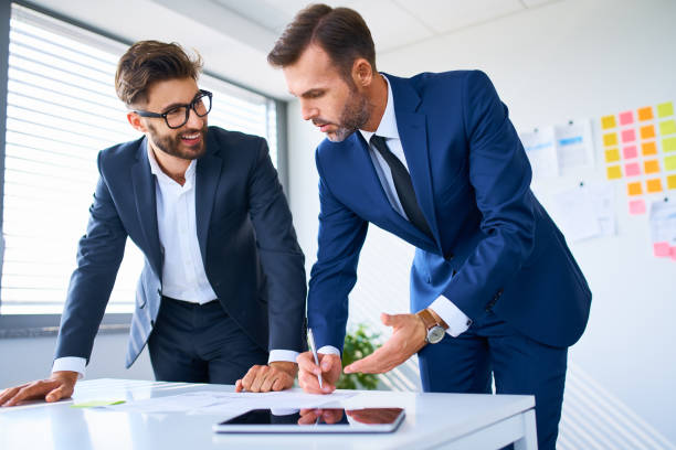 Two business executives looking at documents and discussing in office stock photo