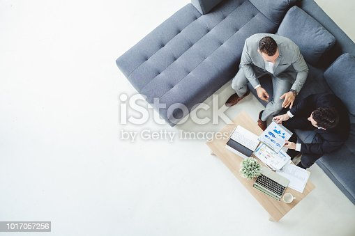 Two business man discussing work on table in office, top view