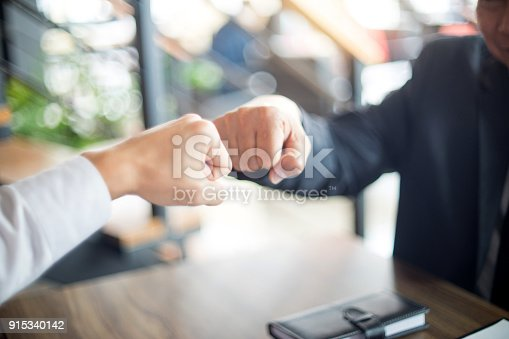 istock two business man use hand to fist bump 915340142