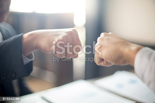 istock two business man use hand to fist bump 915340286